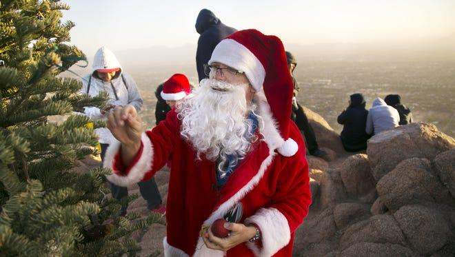 """John Cressey of Scottsdale, who is the """"Camelback Santa,"""" puts an ornament on the Christmas tree on the summit of Camelback Mountain in Phoenix on Saturday, Dec. 17, 2016. Cressey climbs to the top of Camelback a dozen times in December through Christmas taking pictures with people on the summit and giving them candy canes. He has been doing this for four years."""