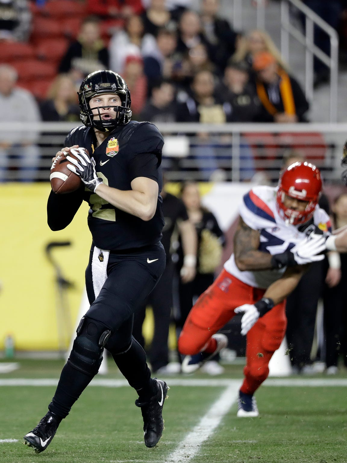 Purdue quarterback Elijah Sindelar, left, throws against