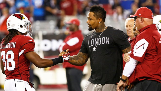 Andre Ellington greets Darnell Dockett before playing the San Diego Chargers during Monday Night Football on Sep. 8, 2014 at University of Phoenix Stadium in Glendale. Dockett suffered a season ending ACL injury in training camp.