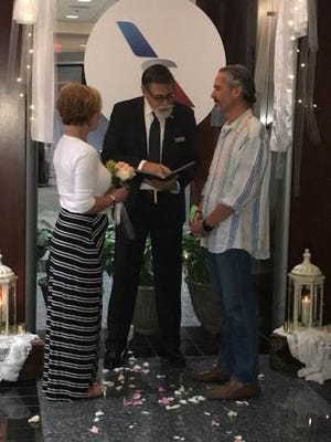 Julie Kay and Vince Bonnetti get married at the American Airlines Admirals Club Thursday in Nashville. Airline employee Terrell Kohn officiated.