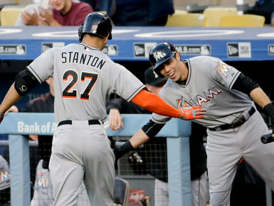 Miami Marlins' Giancarlo Stanton celebrates after his home run with Christian Yelich during first inning of a baseball game against the Los Angeles Dodgers in Los Angeles, Tuesday, May 12, 2015. (AP Photo/Chris Carlson)