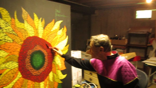 Alexandria native Paul Brewer works on a painting of a sunflower in the basement studio of his home in Lake Forest, Illinois.