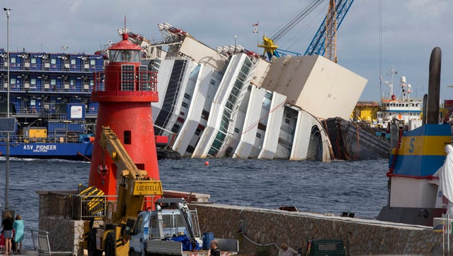 A lighthouse is seen in front of the Costa Concordia as it lies on its side, on the Tuscan Island of Giglio, Italy, Sunday.