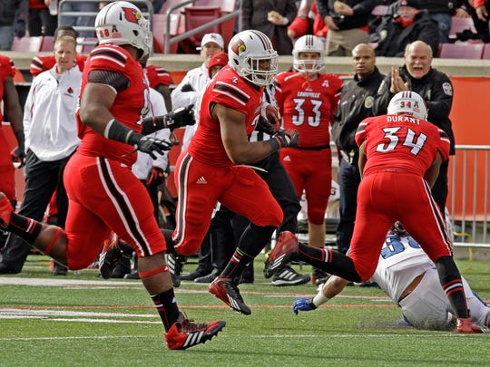 Louisville linebacker Preston Brown gets a block from a teammate as he returns a fumble 48 yards for a touchdown against Memphis on Nov. 23, 2013.