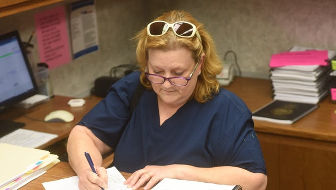 Bonnie Sutterfield completes her paperwork Thursday to run for re-election to the Big Flat City Council.