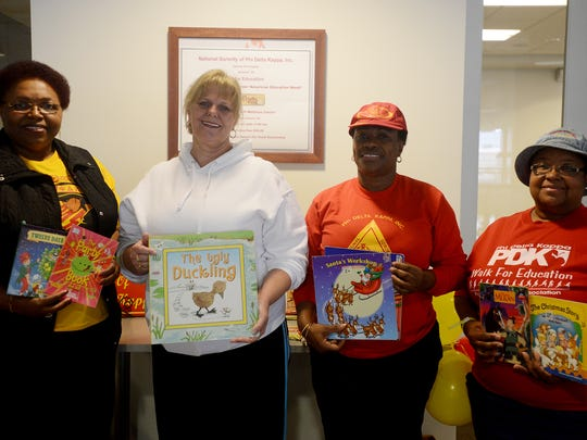 Roslyn Wilson, Gail Gustafson, Delois Dailey and Rose Anderson hold up books during the Gamma Psi Chapter of Phi Delta Kappa Sorority's ninth annual Walk for Education on Saturday at the LIFT Wellness Center in downtown Jackson. The books are being donated to the Dream Center.