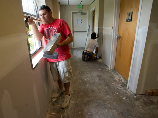 Alex Sanchez, left, and Paul Romero, right, works to help restore the Florida Institute for Human and Machine Cognition building in the wake of April's flooding.