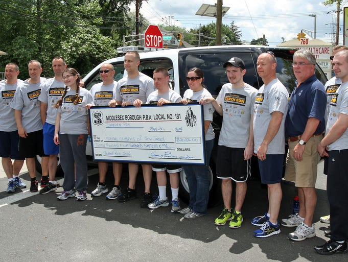 Members of the Middlesex Police Department and some Special Olympics runners line up for a photo with a $20,000 donation check that represents money donated through the Middlesex and Dunellen PBA groups. Some of them were about to join in the run. Members of the law enforcement community and some Special Olympics runners, participate in the Torch Run that is traveling along Route 28 as they pass through Middlesex County and into Somerset County, May 30, 2014. Middlesex NJ. Photo by Kathy Johnson BRI EST 0531 Torch Run