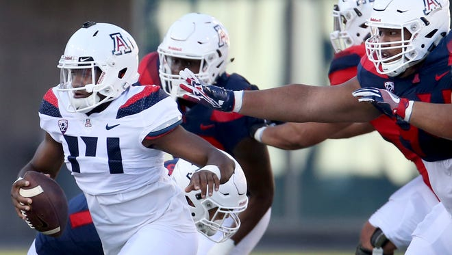 Quarterback Khalil Tate tries to run out trouble and the reach of lineman Stone Taufahema at the University of Arizona's spring game in Arizona Stadium, Saturday, April 14, 2018, Tucson, Ariz.