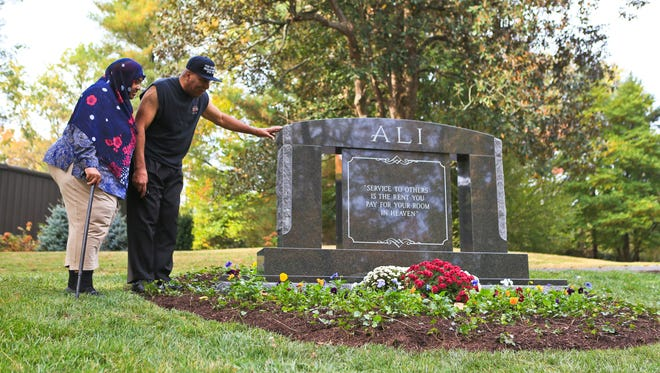 """Rahman Ali touches the monument to Muhammad Ali while visiting his brother's newly completed gravesite Thursday morning at Cave Hill Cemetery. """"This is beautiful,"""" he said. """"Just like he was."""""""
