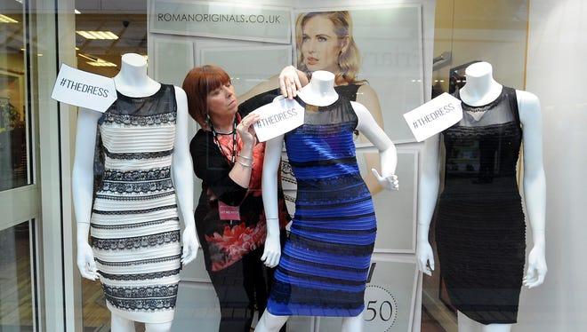 Shop manager Debbie Armstrong adjusts a two tone Roman Originals dress in a window display at a Roman Originals shop in Lichfield, England.