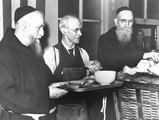 Father Solanus Casey (far right) serves bread in 1942.