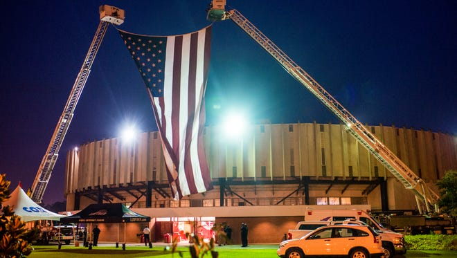 The American flag is suspended from two Lafayette Fire Department engines during a memorial event for the victims of the Grand Theatre shooting at the Blackham Coliseum in Lafayette, La., Thursday, July 30, 2015.