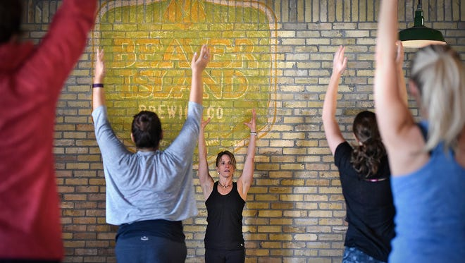 Instructor Chris Haukos leads Saturday's yoga class at Beaver Island Brewing Co. in St. Cloud. After the class, participants were able to enjoy flights or pints of beer.