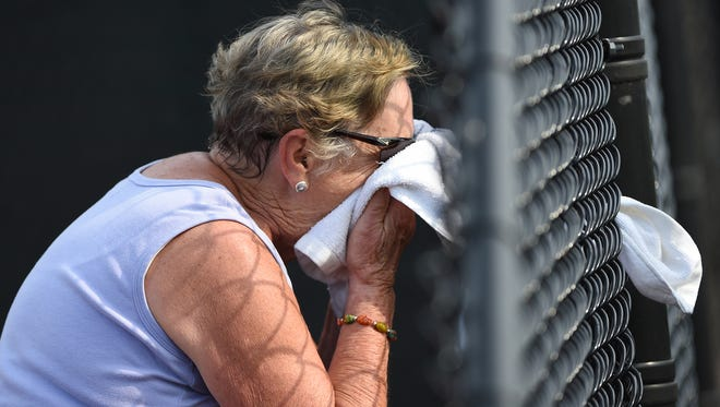 Judy Mitchell of Lancaster wipes sweat off her face after warming up for her mixed tennis match for the Keystone State Games at Central York High School. Wellspan will have a staff of 25 physicians and 16 trainers volunteering to keep athletes safe during the games.