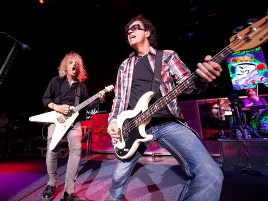 C.C. Deville (L) and Bobby Dall of Poison perform.