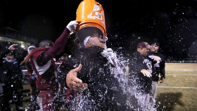 Madison county football coach Mike Coe is drenched by his players as they celebrate a win over Pahokee during a 2017 state semifinal.