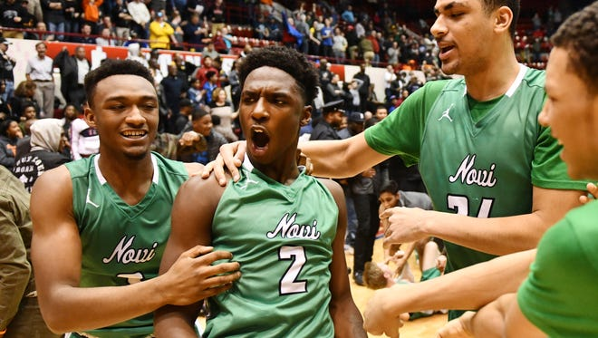 Wildcats' Traveon Maddox Jr. celebrates his game winning two point shot, 75-73, with his teammates.