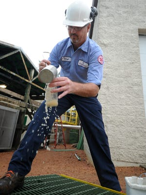 A waste treatment operator scoops up a sample to be tested at Foremost Farms in 2011.