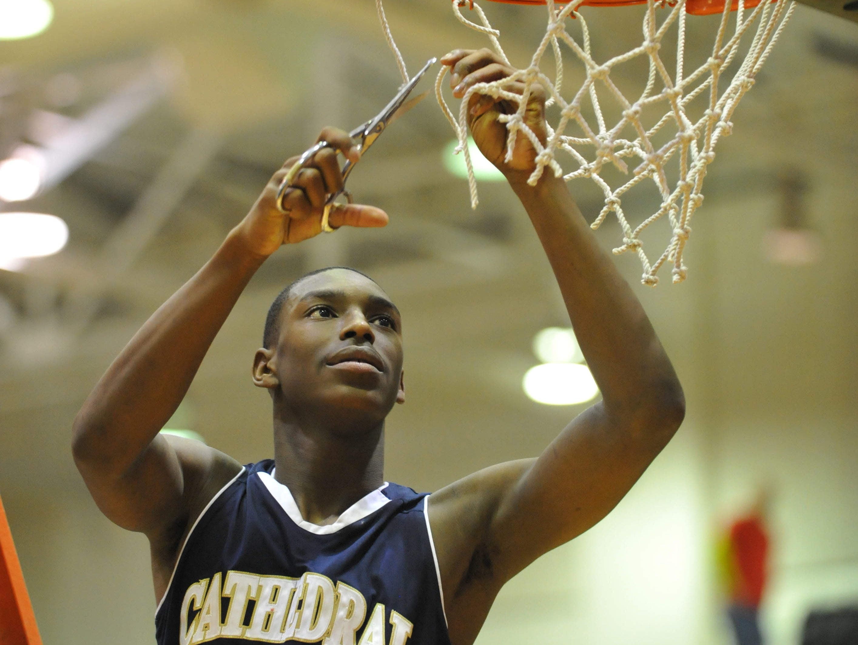 FILE — Cathedral's Jalen Coleman cuts down a piece of the net after Cathedral defeated Tech to win the City Championship, Jan. 21, 2013.
