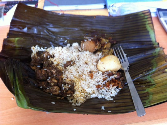 """Chicken Lamprasi, which is grilled chicken, rice, a hard-boiled egg and a """"cutlet"""" wrapped in a banana leaf and steamed. Unlike our """"cutlet"""" over here, it was a thickly breaded chopped meat filled item that reminded me of a tamale but seasoned differently."""