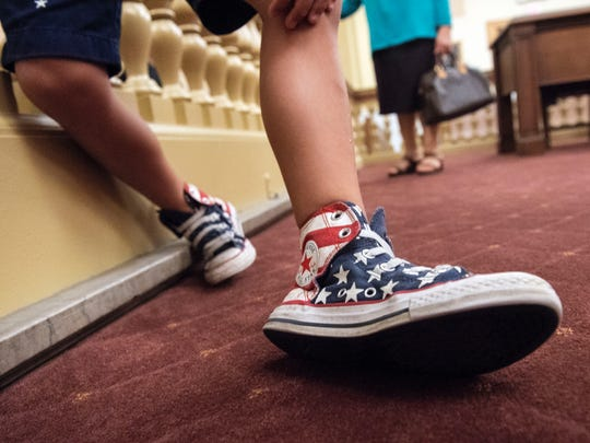 Piero Faraone, 5, shoes off his American flag themed sneakers following the naturalization ceremony. Forty-seven people from more than 20 different countries became U.S. citizens on Thursday, June 28, 2018, during a national