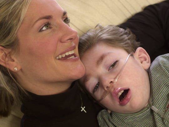 Jill Kelly smiles as she holds Hunter in their Orchard Park home on Jan. 25, 2001.