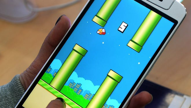 Flappy Bird game displayed on a smartphone.