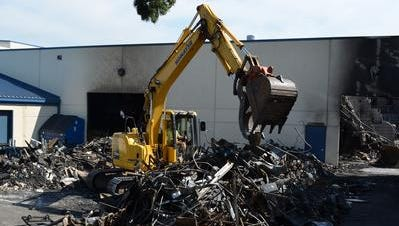 An excavator picks through the items pulled from the damaged building at Woodburn High School: metal to the right and rubble to the left.