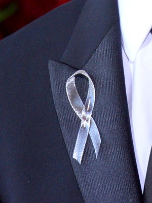 George C. Wolfe wears a silver ribbon on his lapel as he arrives at the Tony Awards.