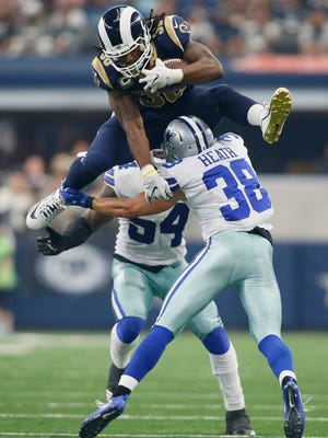 Los Angeles Rams running back Todd Gurley (30) hurdles over Dallas Cowboys safety Jeff Heath (38) in the third quarter at AT&T Stadium.