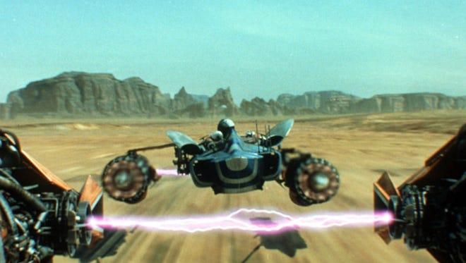 "Pod racers scoot over a desert-like landscape in ""Star Wars."""