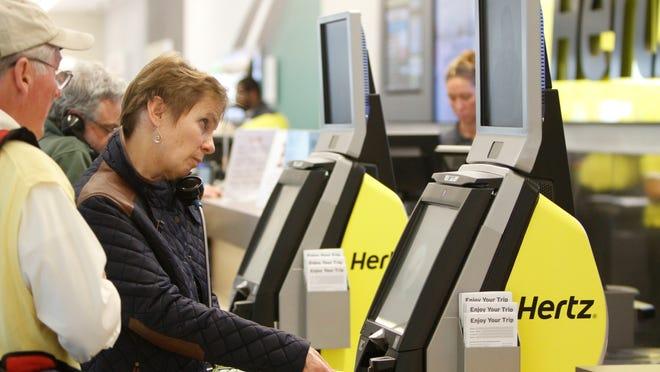 Wellesley, Massachusetts, residents Tony and Mary Ann Powell use a self-service kiosk to reserve a Hertz rental car Thursday at Southwest Florida International Airport.