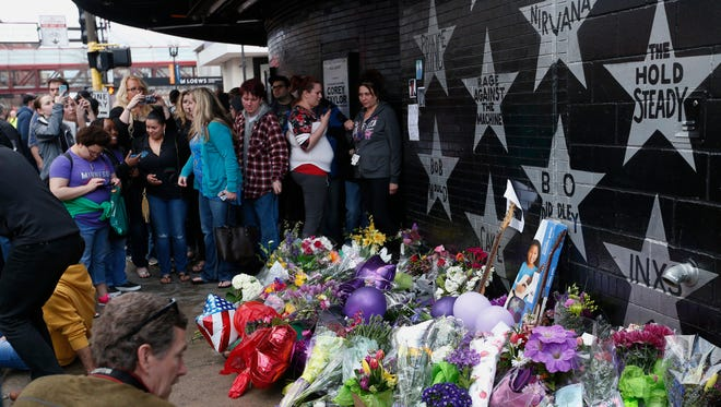 People gather at a memorial created below Prince's star, center top, adorning the wall of First Avenue, where the pop super star Prince often performed, in Minneapolis April 21, 2016.