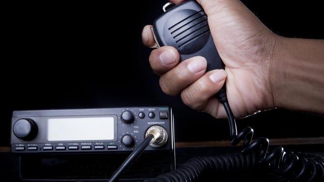Hand of amateur radio holding speaker.
