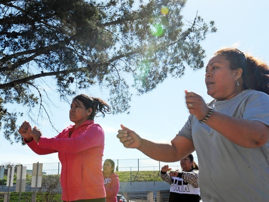 Graciela Vega, right, works out during Zumba class