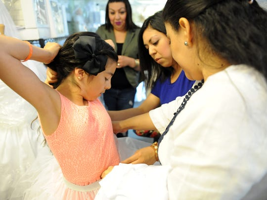 Jalyssa Garibay, 9, is fitted for a First Communion dress at Alicia's Boutique in Salinas. Attending her is Ana Suarez, right, and Jalyssa's godmother Leslie Garibay, in blue, and mother Lety in green.