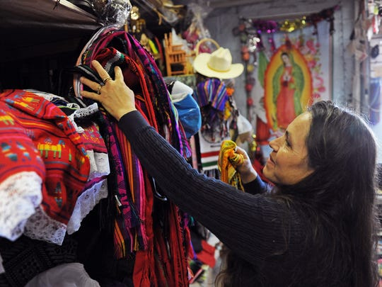 Arranging stock at Amalia's Toys, Maria Rodriguez is happy to share the item's provenance.