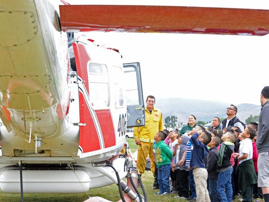 Students from Jesse B. Sanchez Elementary School gaze up at the Bear Vallet Helitack helicopter at Wednesday's annual Emergency Medical Services Week event at the Constitution Soccer Complex in Salinas.