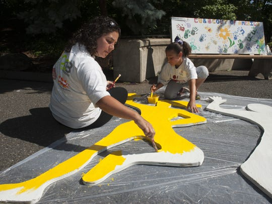 Volunteers Michelle Conti of Cherry Hill and her daughter Isabella, 9, work to revitalize the Camden Children's Garden. Thursday, June 25, 2015.