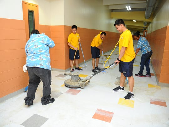 Petty Officer 3rd Class Mark Rivera operates a floor buffer as he, fellow shipmates from the U.S.S. Chancellorsville and Guam Cleaning Masters employees strip old wax from the floor of C.L. Taitano Elementary School in Sinajana for the next school on Tuesday, July 28. Sailors from the ship were scheduled to offer their help in the community at the school, Agana Heights Elementary School and the Sinajana Community Center, according to a Navy release.