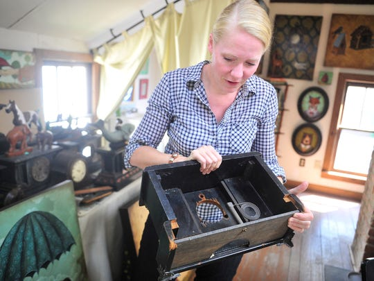 Local painter Elizabeth Foster holds a clock that she makes art out of when she is not painting.