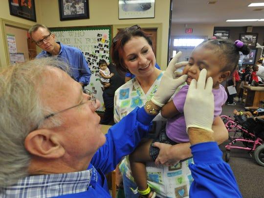 Volunteer dentists help provide needy children with dental care.