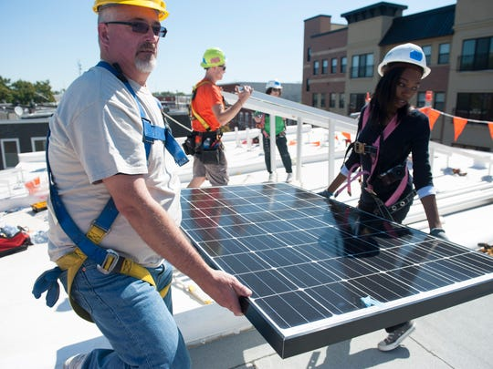 Volunteers with PSE&G Joe Prusic and Fay Muhammad carry a solar panel as Low-income homes in East Camden get solar panels installed at no cost thanks to a partnership among PSE&G, GRID Alternatives Garden State, NeighborhoodWorks America and St. Joseph's Carpenter Society. Tuesday, September 15, 2015.