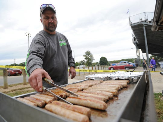 JC Wisecup flips brats on a grill Friday at the Unioto