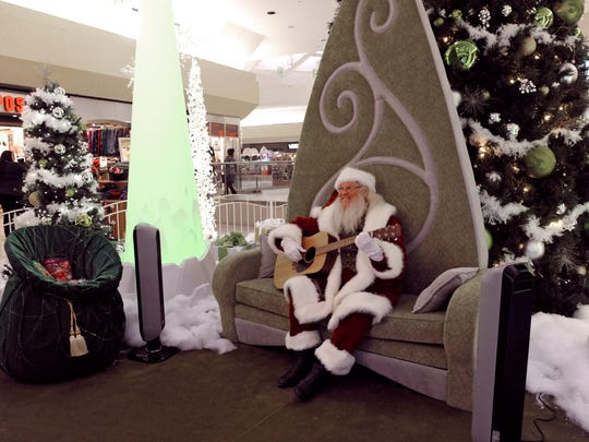 Santa strums his guitar while waiting for children at Meadowood Mall in November 2014. Barone's analysis concludes that Q4 growth should show stronger growth and lead to healthy holiday sales.