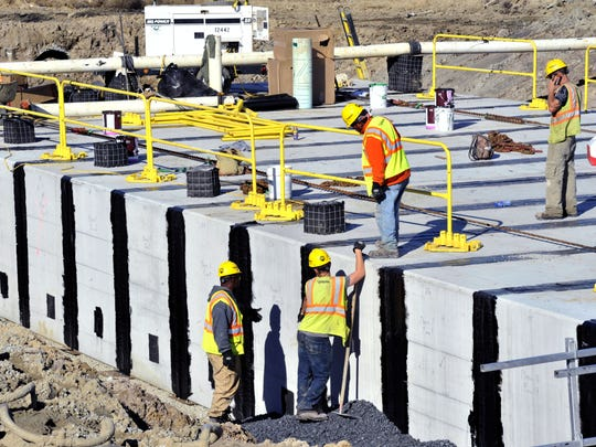 Workers busy pouring cement at Dover AFB's $98.3 million runway replacement project Thursday.