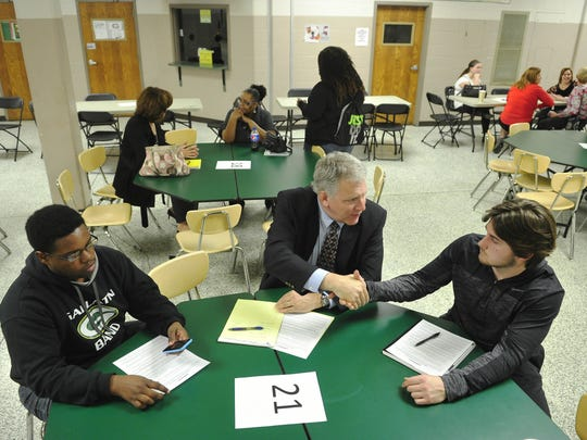 Tennessee Promise mentor Jim Hawkins, center, shakes Tristan Rogers' hand at a March 2015 meeting.