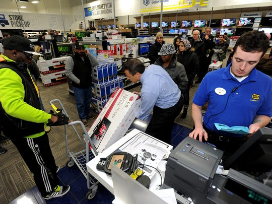 A Best Buy employee rings up a 32-inch LED TV on Black Friday in this Nov. 29, 2013, file photo.