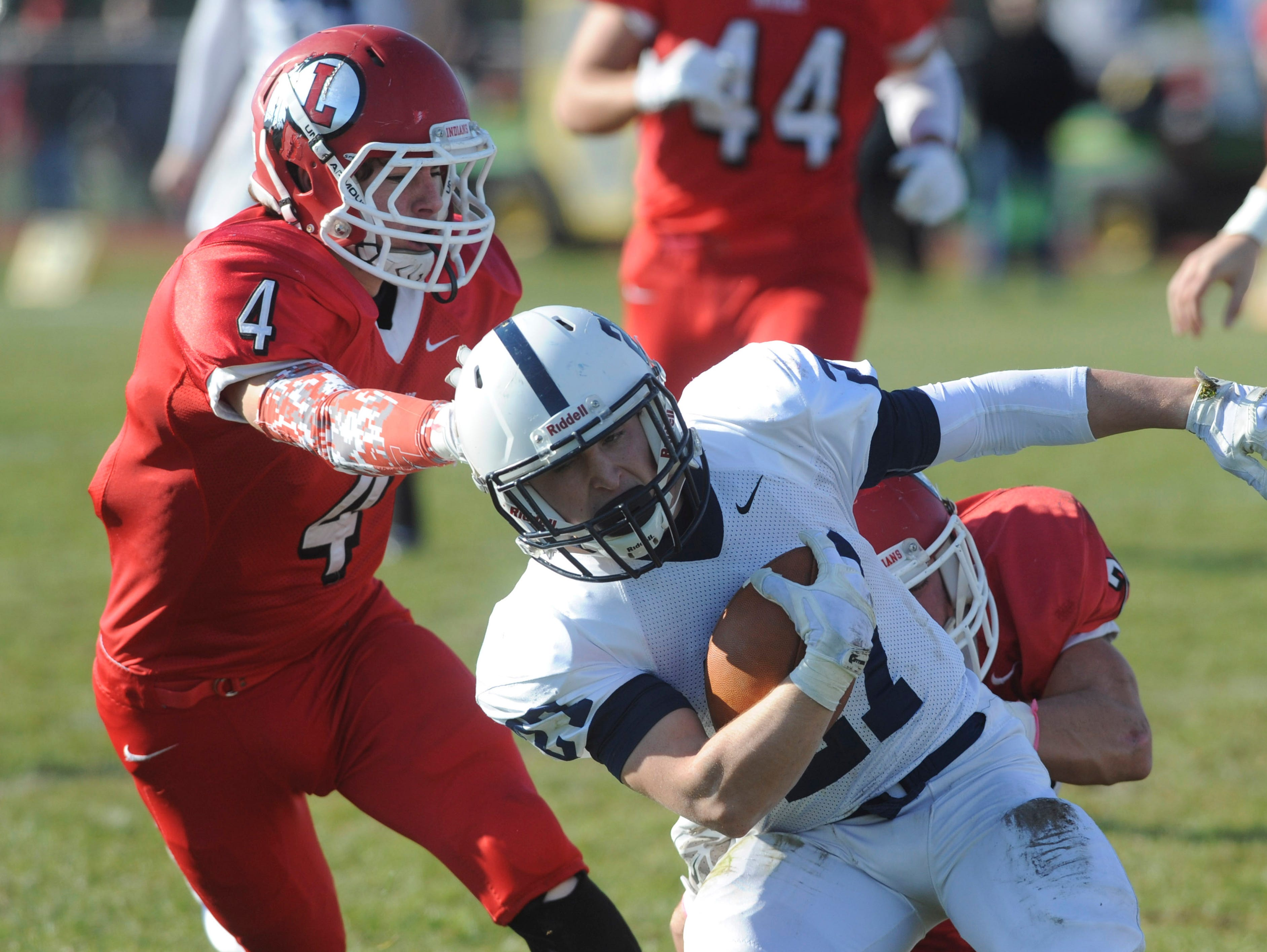 Shawnee's Michael Githens is brought down by Lenape's Ryan Shuts and Tim Montgomery (left) during Thursday's Thanksgiving Day football game at Lenape. Thursday, November 26, 2015.
